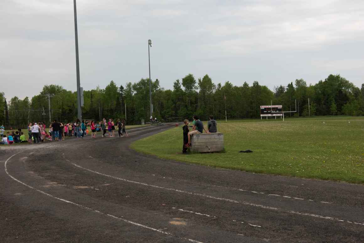 Students stand on a run-down running track. Several of the students sit on a wooden box placed on a lawn to the right.