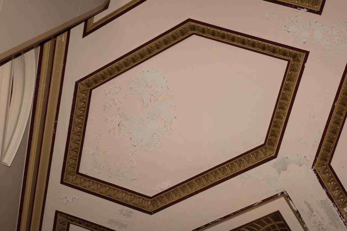Plaster peels and flakes off of the walls of the 1960s-era auditorium at Muskegon High School. Plaster has not been replaced since the wing of the school was constructed.