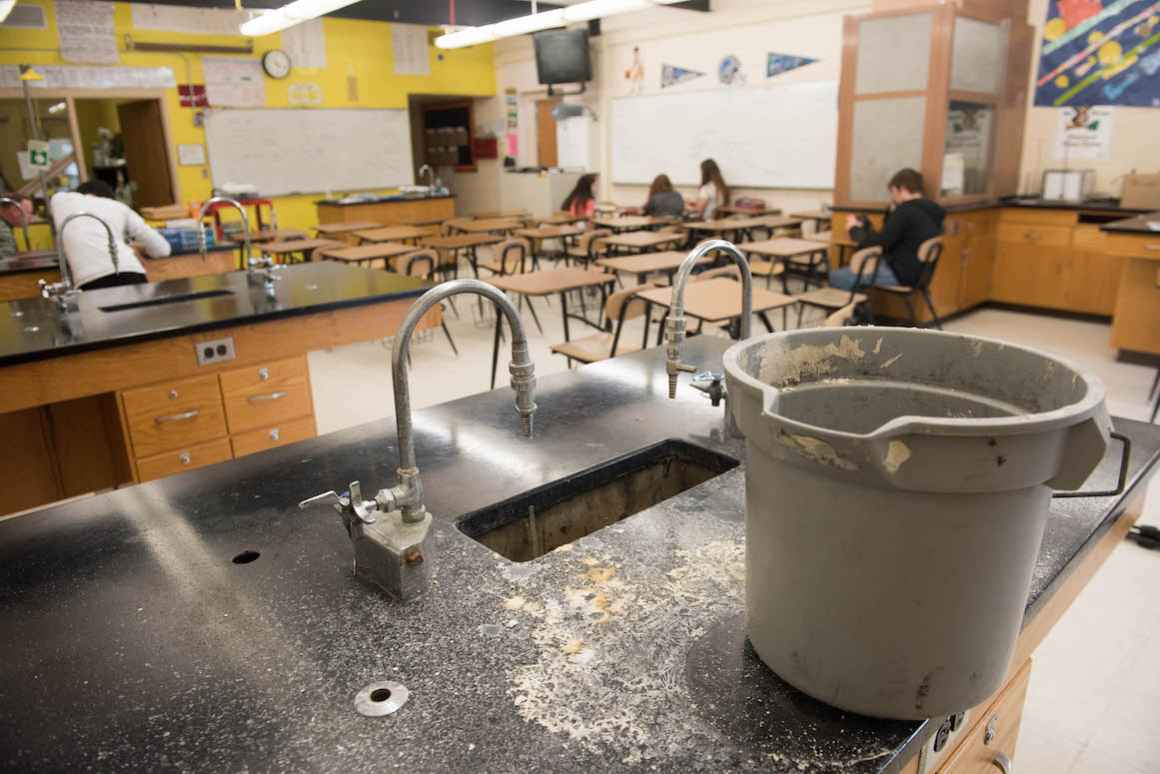 In the high school chemistry lab, a roof leak has made one of the lab stations unusable.